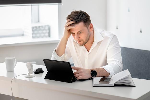 Seitenansichtaufnahme des nachdenklichen jungen mannes, der zu hause sitzt und am laptop arbeitet. kaukasischer mann, der vom hauptbüro arbeitet. Premium Fotos