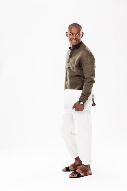 Seitenansichtbild in voller länge des lächelnden afrikanischen mannes, der tablet-computer hält und zurückblickt Kostenlose Fotos