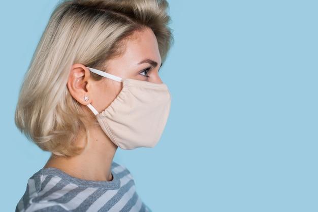 Seitenansichtfoto einer blonden kaukasischen frau, die eine medizinische maske trägt, die auf den blauen freien raum nahe ihr schaut Premium Fotos