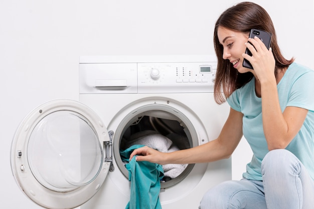 Seitenansichtfrau, die am telefon in der waschküche spricht ...