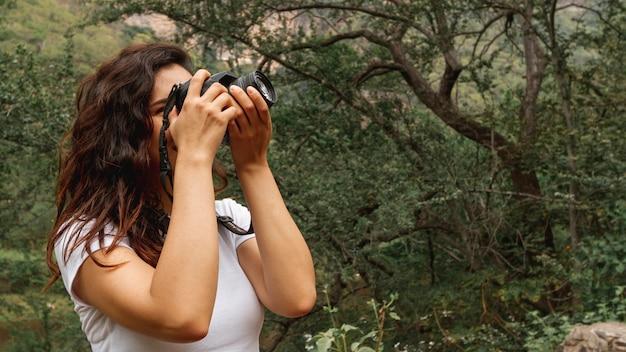 Seitenansichtfrau, die fotos der natur macht Kostenlose Fotos