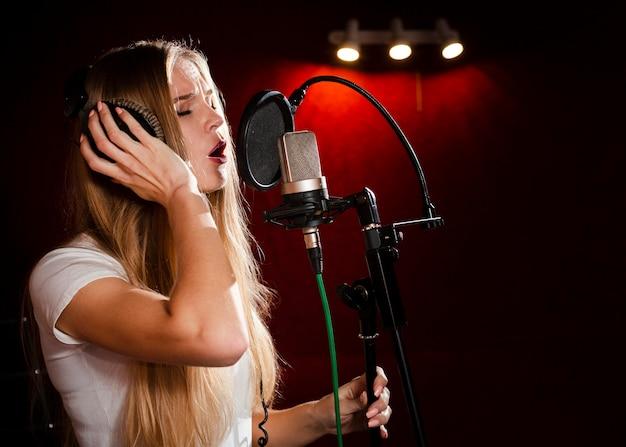 Seitenansichtfrau, die im mikrofon singt und kopfhörer trägt Premium Fotos