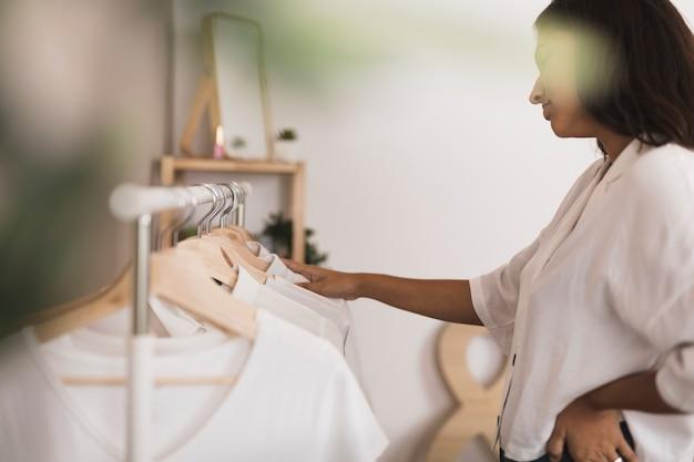 Seitenansichtfrau, die in der garderobe in n schaut Kostenlose Fotos