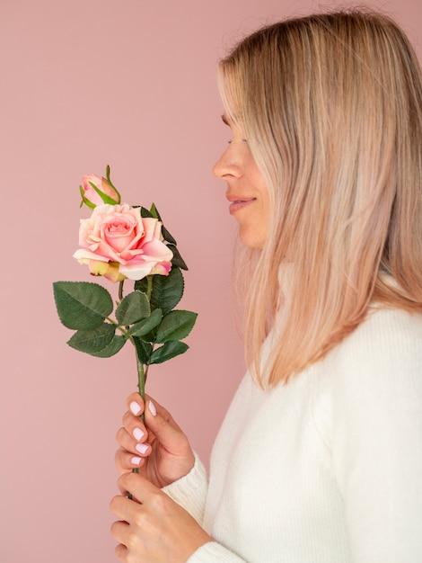 Seitenansichtfrau, die schöne rose hält Kostenlose Fotos