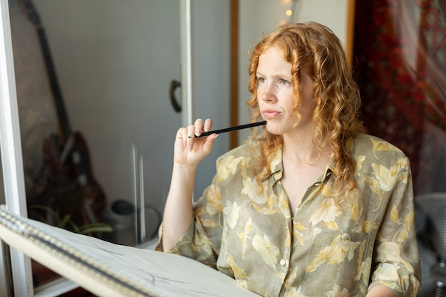Seitenansichtfrau mit dem bleistiftdenken Kostenlose Fotos