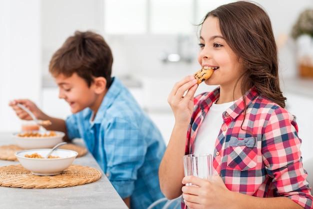 Seitenansichtgeschwister, die morgens frühstück essen Kostenlose Fotos