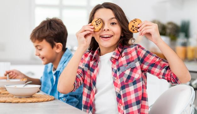 Seitenansichtgeschwister, die spaß während des frühstücks haben Kostenlose Fotos