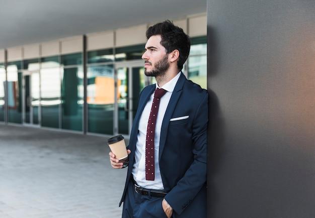 Seitenansichtmann mit dem kaffee, der weg schaut Kostenlose Fotos