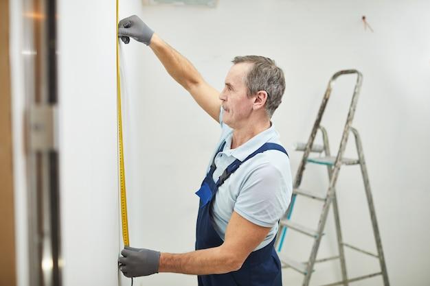 Seitenansichtporträt des leitenden bauarbeiters, der wand misst, während haus renoviert, raum kopiert Premium Fotos