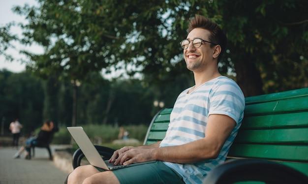Seitenansichtporträt eines jungen selbstbewussten männlichen freiberuflers, der an seinem laptop arbeitet, während er auf einem strand im park sitzt und lächelnd wegschaut. Premium Fotos