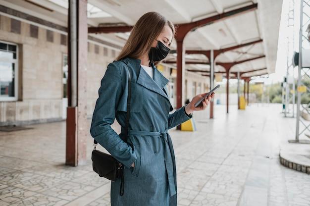 Seitenansichtsfrau, die ihr handy prüft Premium Fotos