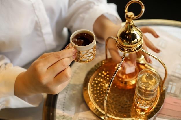 Seitenansichtsfrau, die türkischen kaffee mit türkischem vergnügen und einem glas wasser trinkt Kostenlose Fotos