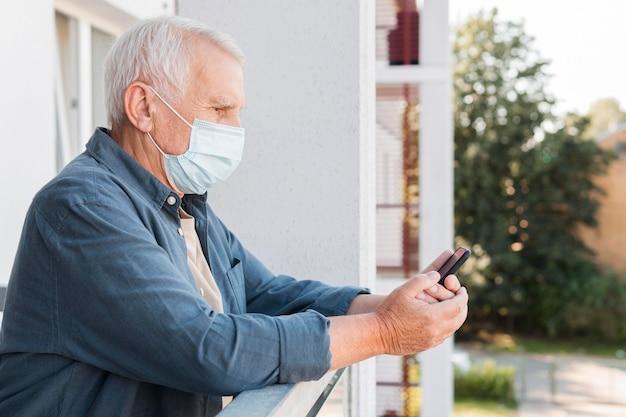 Seitenansichtsmann mit telefon tragender maske Premium Fotos