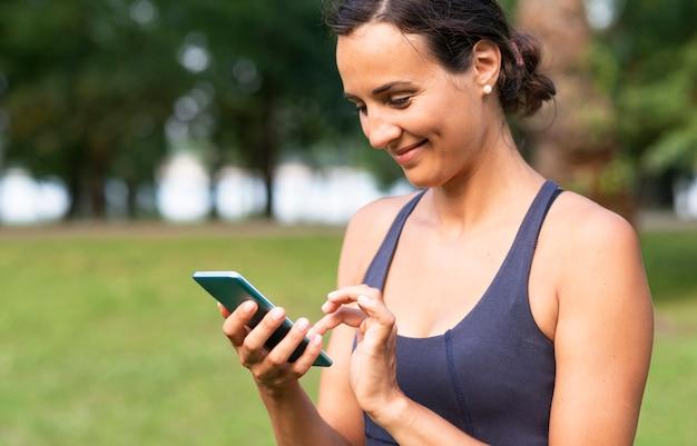 Seitenansichtsmileyfrau mit smartphone Kostenlose Fotos