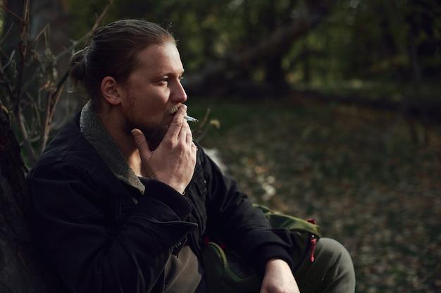 Seitenporträt eines rauchenden jungen bärtigen abenteurers, der sich im herbstwald entspannt Premium Fotos