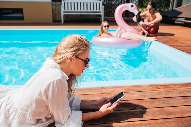 Seitlich frau, die ihr telefon am pool überprüft Kostenlose Fotos