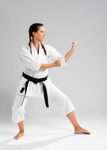 Seitlich karatefrau im traditionellen weißen kimono auf weißem hintergrund Kostenlose Fotos