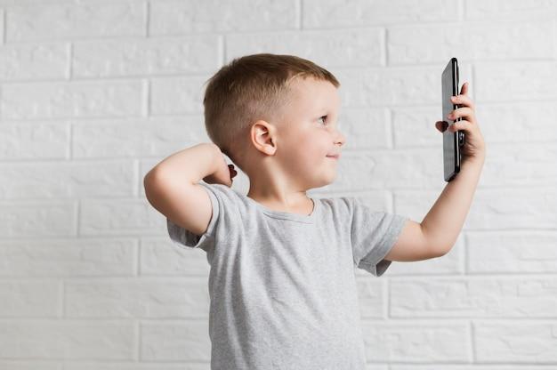 Seitlich kleiner junge, der ein selfie nimmt Kostenlose Fotos