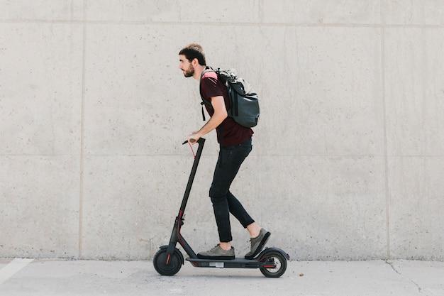 Seitlich mann, der e-roller reitet Kostenlose Fotos