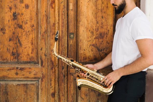 Seitlich saxophonist mit hölzernem hintergrund Kostenlose Fotos