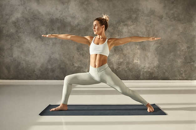 Seitliches vollbild einer attraktiven muskulösen jungen frau, die hatha yoga im fitnessstudio praktiziert und barfuß auf einer matte in virabhadrasana 2 oder warrior two-pose steht und einen konzentrierten gesichtsausdruck hat Kostenlose Fotos