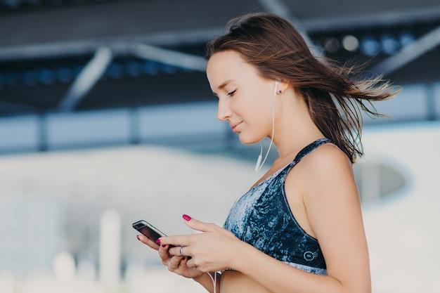 Seitwärts geschossen von der sportlichen reizenden frau mit dem dunklen haar, gekleidet in der zufälligen ausstattung, hält modernes intelligentes telefon Premium Fotos