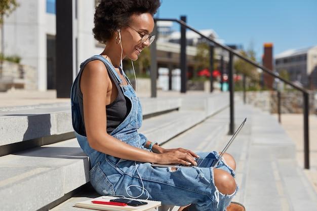 Seitwärts geschossen von entspannter sorgloser junger dame mit knackigem haar, hört radio in kopfhörern, tastaturen auf laptop-computer, macht freiberufliche arbeit, tagebuch in der nähe, sitzt auf stufen während des sonnigen tages über stadtblick Kostenlose Fotos