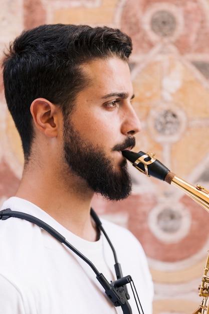 Seitwärts mannportrait, welches das saxophon spielt Kostenlose Fotos