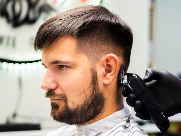Seitwärts person, die einen neuen haarschnitt erhält Kostenlose Fotos