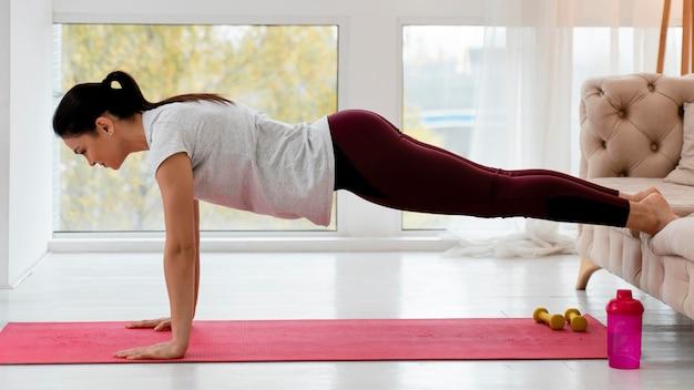 Seitwärts schwangere frau, die yoga zu hause tut Kostenlose Fotos