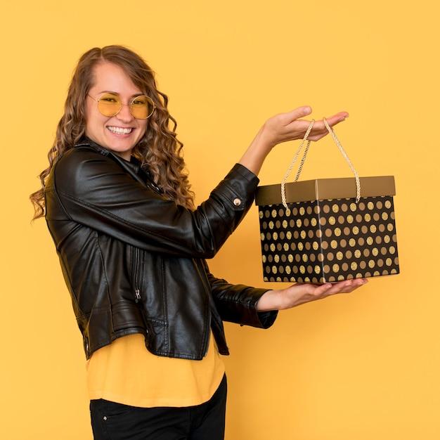 Seitwärts smiley frau hält schwarzen freitag geschenkbox Kostenlose Fotos