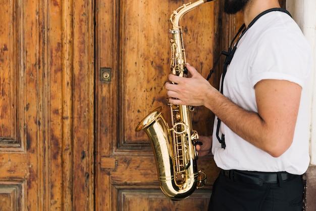 Seitwärtsmusiker, der das saxophon spielt Kostenlose Fotos