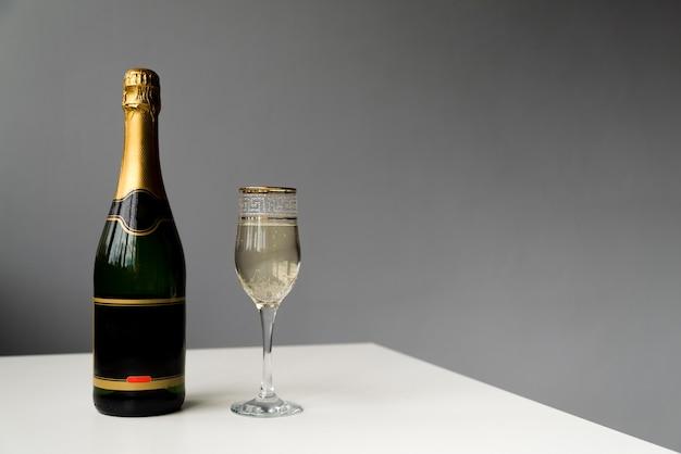 Sektflasche und champagnerglas auf weißer tabelle Kostenlose Fotos