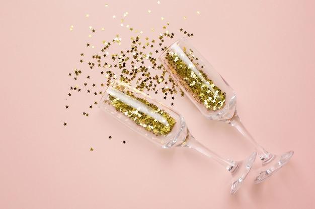 Sektgläser mit goldenen sternen konfetti auf beige Premium Fotos