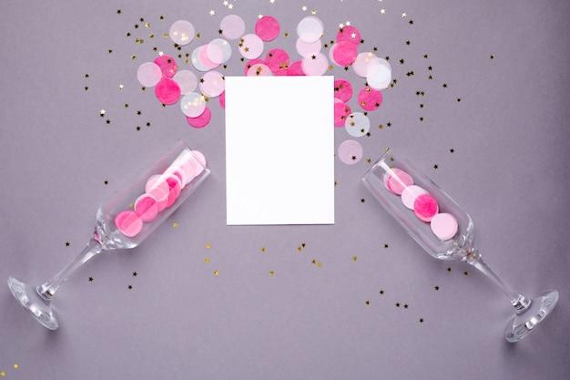 Sektgläser und karte mit rosa konfetti Premium Fotos