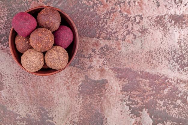Selbst gemachte bunte rohe kakao-energie-bälle des strengen vegetariers in der hölzernen schüssel Premium Fotos