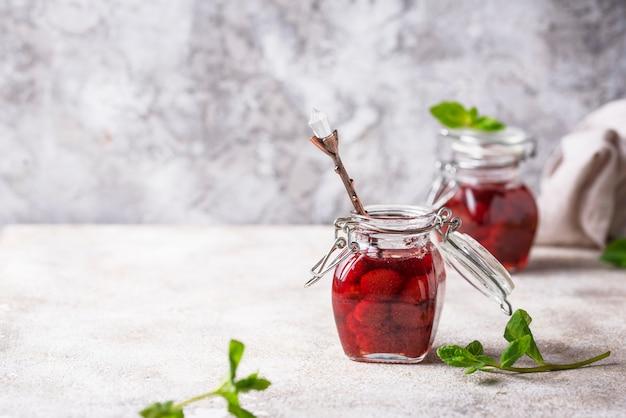 Selbst gemachte erdbeermarmelade im glas Premium Fotos