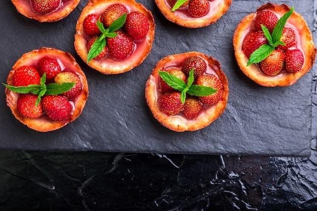 Selbst gemachte erdbeertörtchen auf schieferplatte Premium Fotos