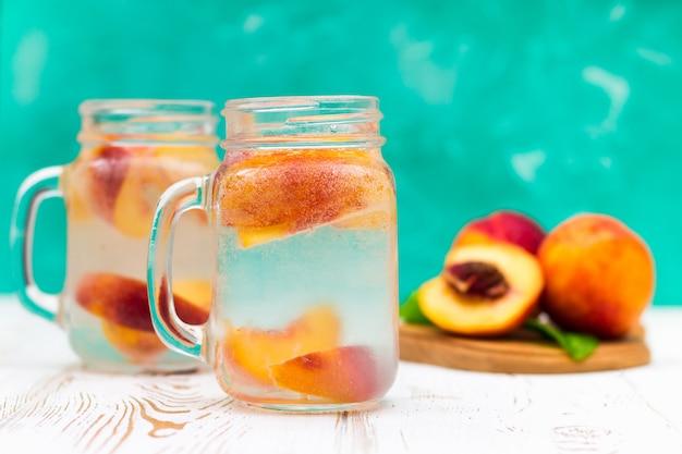 Selbst gemachte gefrorene limonade mit reifen pfirsichen. frischer pfirsicheistee in einem weckglas. Premium Fotos