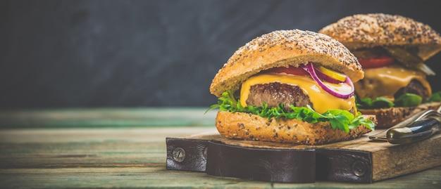 Selbst gemachte hamburger auf hölzernem hintergrund, raum für text Premium Fotos