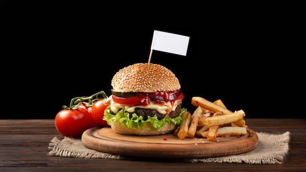 Selbst gemachte hamburgernahaufnahme mit rindfleisch, tomate, kopfsalat, käse und pommes-frites auf schneidebrett. kleine weiße fahne in den burger eingefügt Premium Fotos