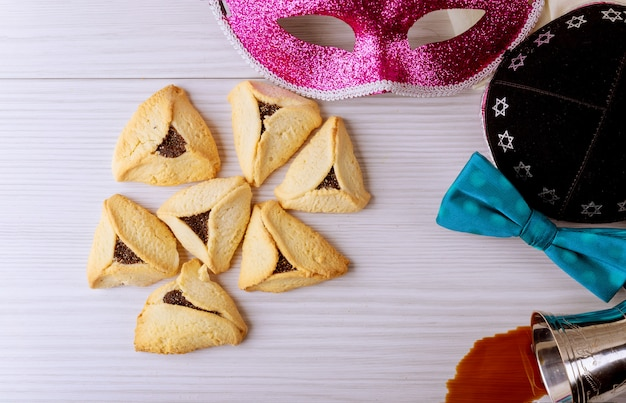 Selbst gemachte kekse der jüdischen purim hamantaschen mit purim maske und rotem koscherem purim kippah Premium Fotos