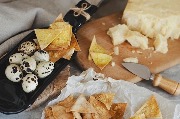 Selbst gemachte knusperige chips vom fladenbrot mit parmesankäseparmesankäse und wachteleiern auf der umhüllungsplatte gemacht von der flasche. Premium Fotos