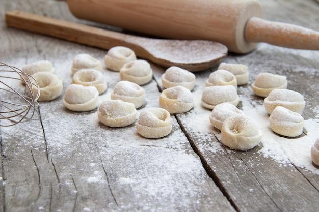 Selbst gemachte mehlklöße mit mehl und küchengeschirr auf rustikalem holztisch. traditionelle russische pelmeni. halbfertige produkte. Premium Fotos