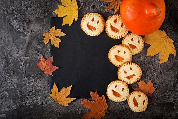 Selbst gemachte plätzchen in der form als halloween-steckfassung-olaternenkürbise auf der dunklen tabelle. ansicht von oben. Kostenlose Fotos