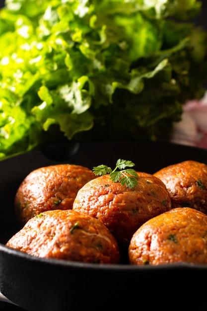 Selbst gemachte rohe organische würzige fleischklöschen des lebensmittels im eisen werfen auf schwarzem hintergrund Premium Fotos