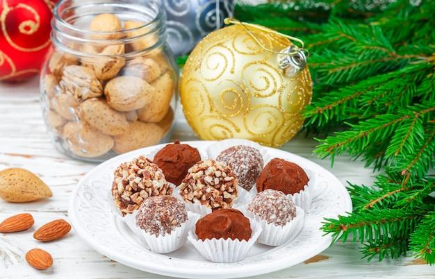 Selbst gemachte schokoladentrüffeln mit mandel-, kokosnuss- und kekskrume in einer weißen platte Premium Fotos