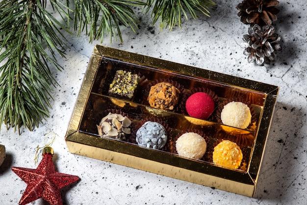 Selbst gemachte schokoladentrüffelsüßigkeiten in einer geschenkbox. zusammenstellung der runden farbigen süßigkeiten Premium Fotos