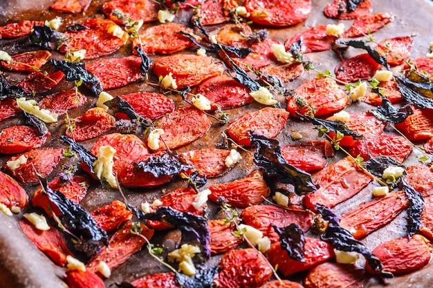 Selbst gemachte sonnengetrocknete tomaten mit basilikum, knoblauch und gewürzen auf papier Premium Fotos