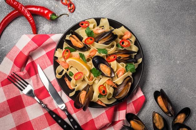 Selbst gemachte teigwaren-spaghettis mit miesmuscheln, paprikas und petersilie auf steinhintergrund. Premium Fotos
